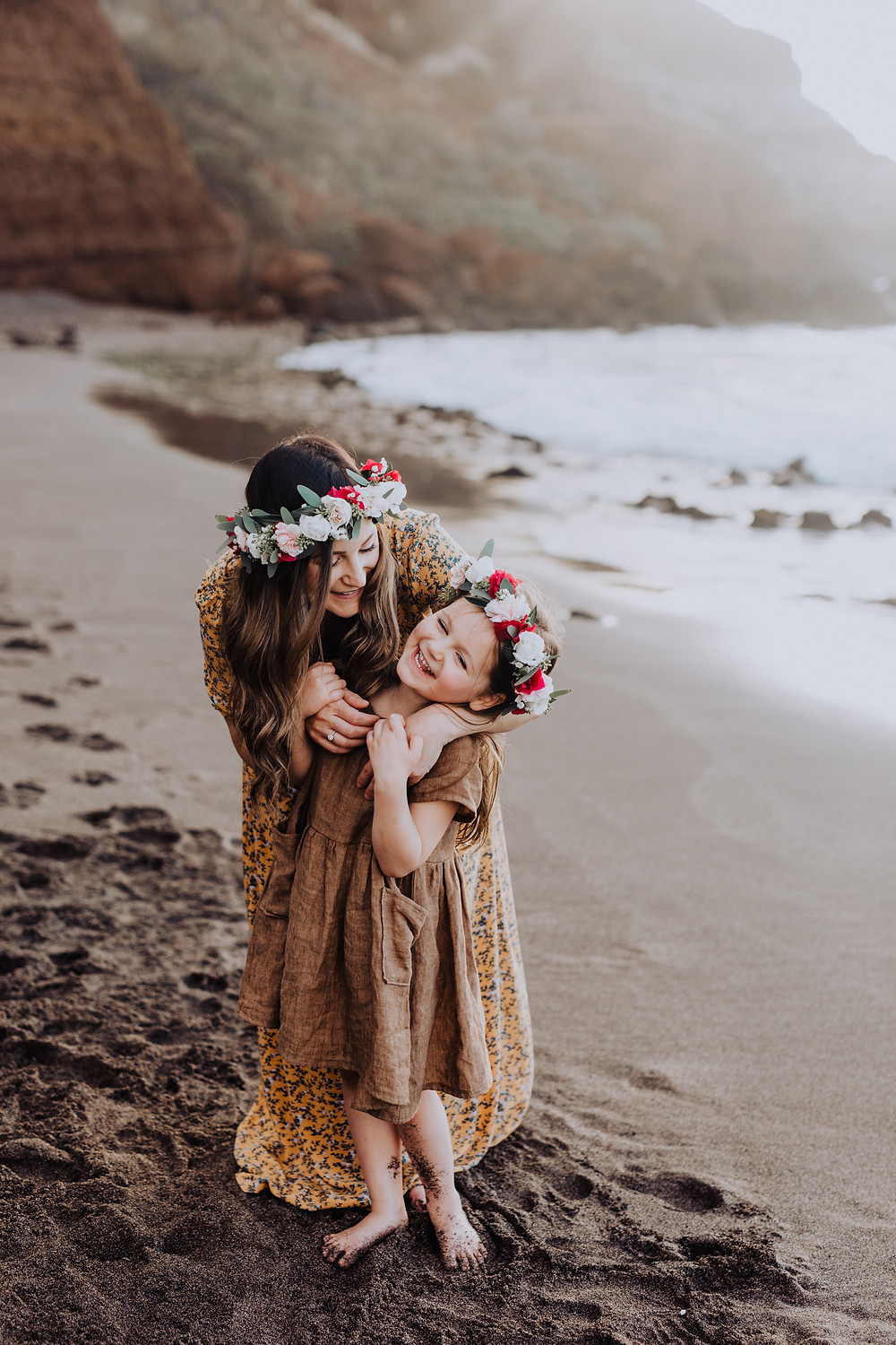 A mother and daughter laugh playfully together on the beach in Hawaii.