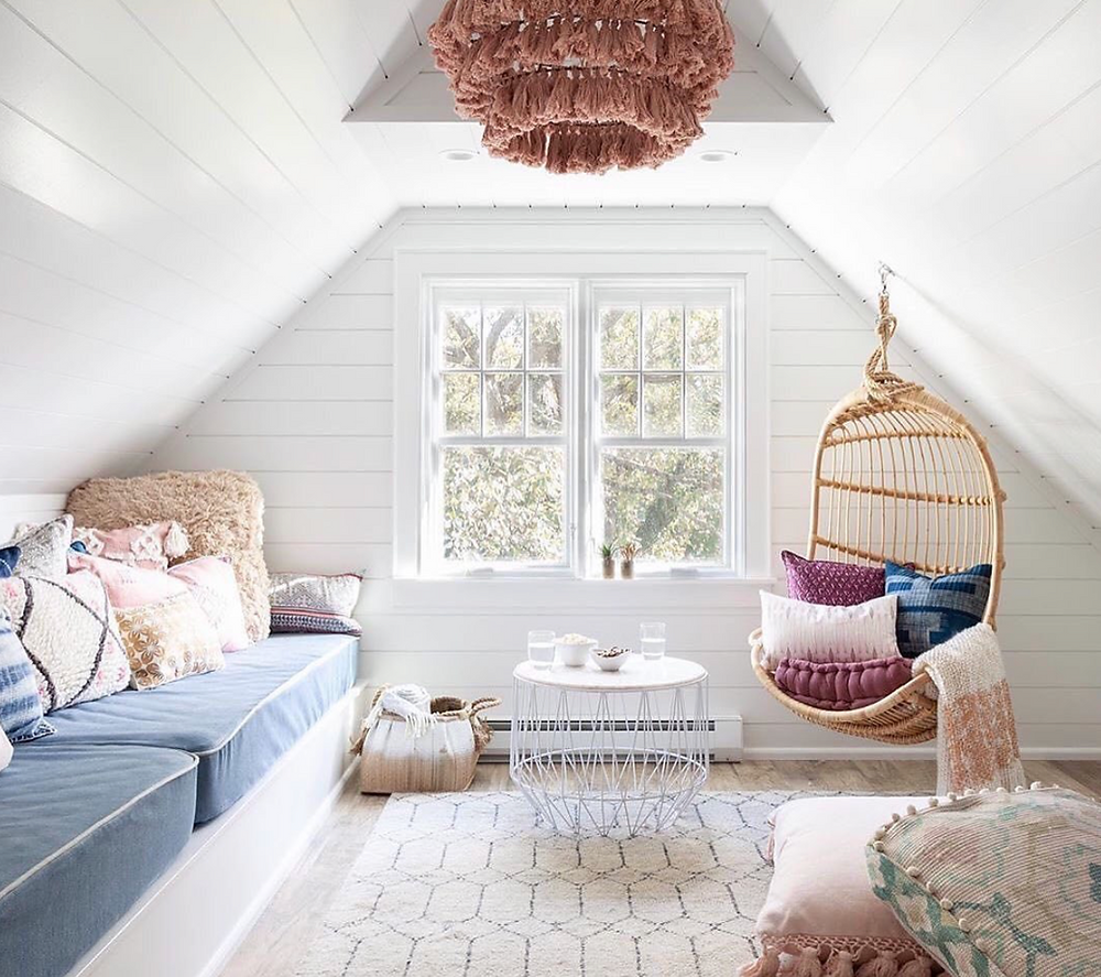 white cottage bedroom nook with blue and lavender cushions and hanging rattan chair with a white area rug and a boho chic light pendant from anthropologie