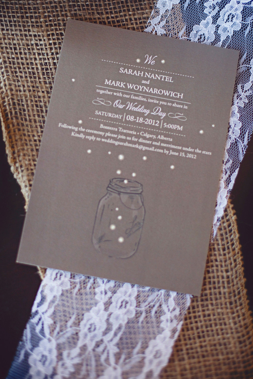 A brown rustic wedding invitation laying on a piece of lace and burlap.