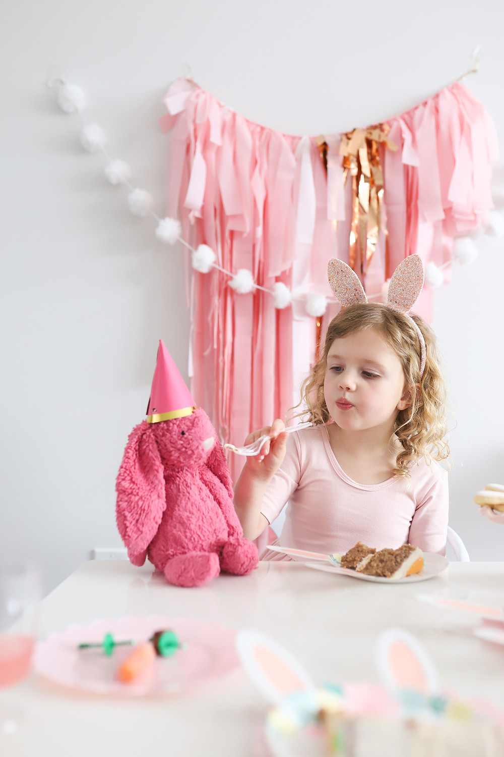 A little girl sitting with a pink stuffed bunny wearing a party hat for a birthday celebration.