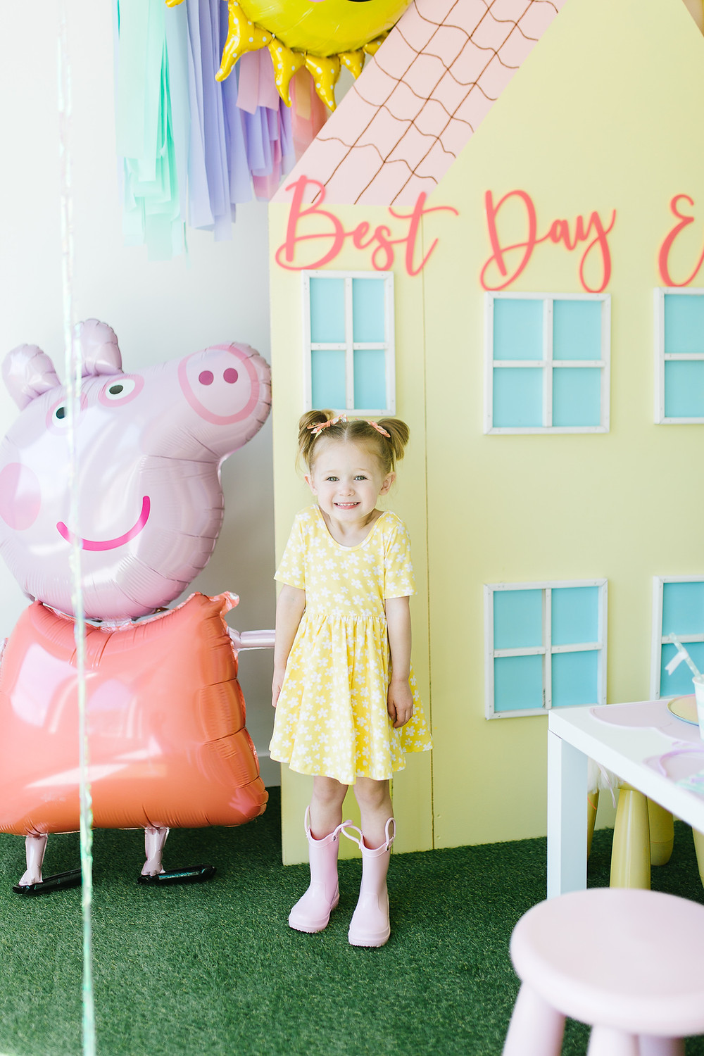 Little girl at a Peppa Pig birthday party with pastel colours streamers and little white tables and colored stools