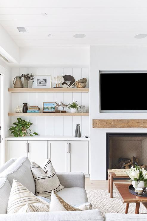 shiplap ceiling shiplap wall details wood open shelves storage fireplace with wood mantle tv over mantle large grey sectional with throw pillows wooden coffee table bench wool jute area rug