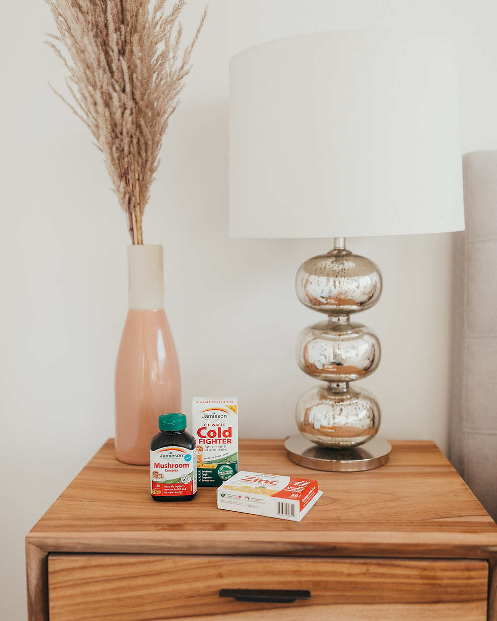 A bedroom bedside table with some health supplements sitting on top.