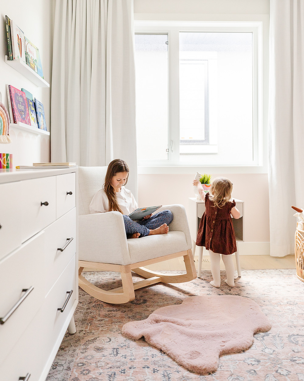 A boho modern baby girls nursery with llama and cactus wallpaper, a blush pink rug, a white monte designs joya rocking chair, a beaded light pendant, a white crib and a scalloped pink wall behind white drapery.
