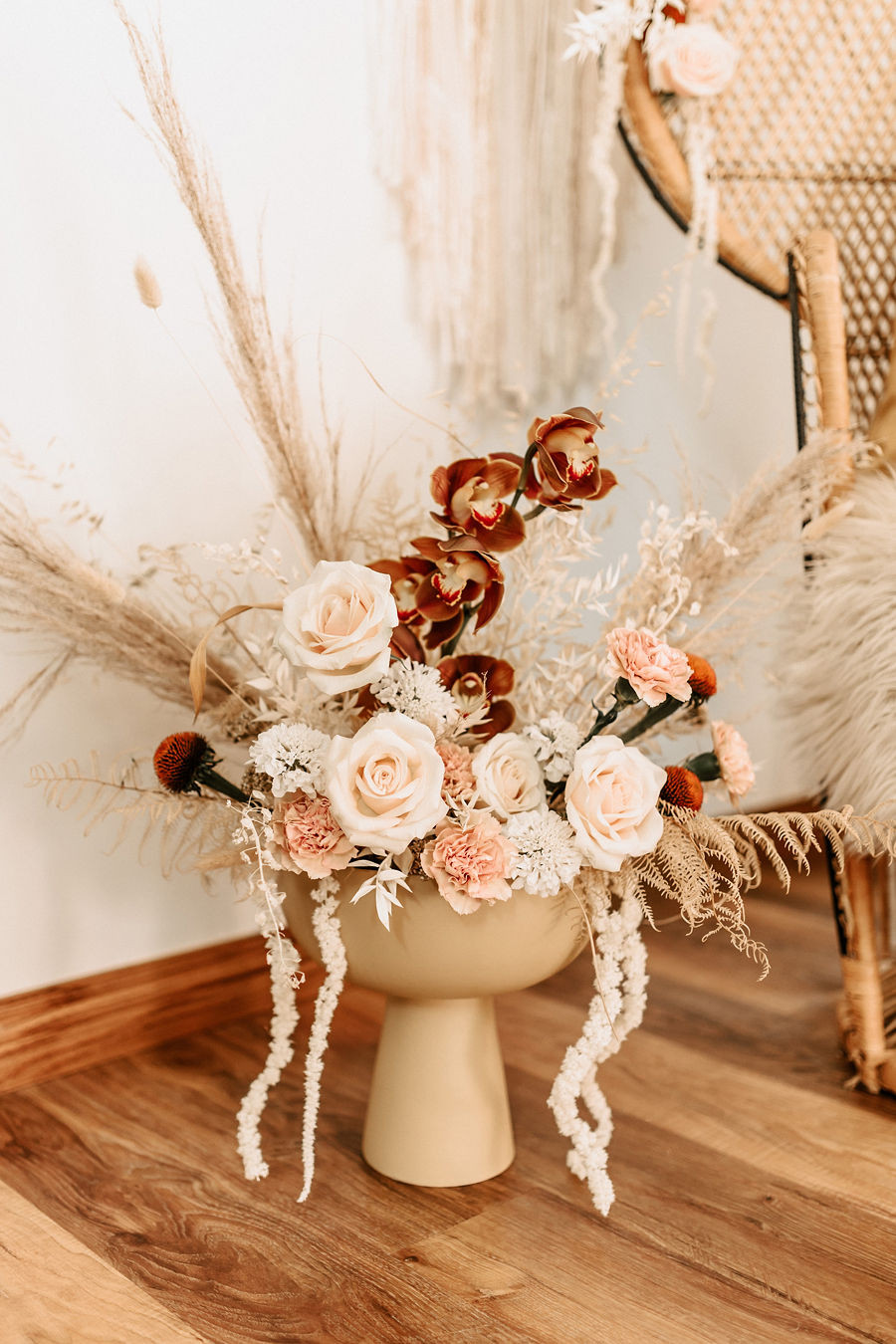 A collection of vintage boho romantic inspired flowers at a baby shower with lace details and whicker accents.