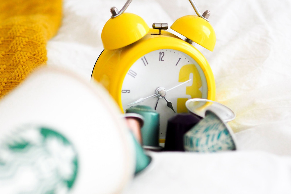 A yellow alarm clock with black hands sitting against a white background of bedding next to a yellow blanket.