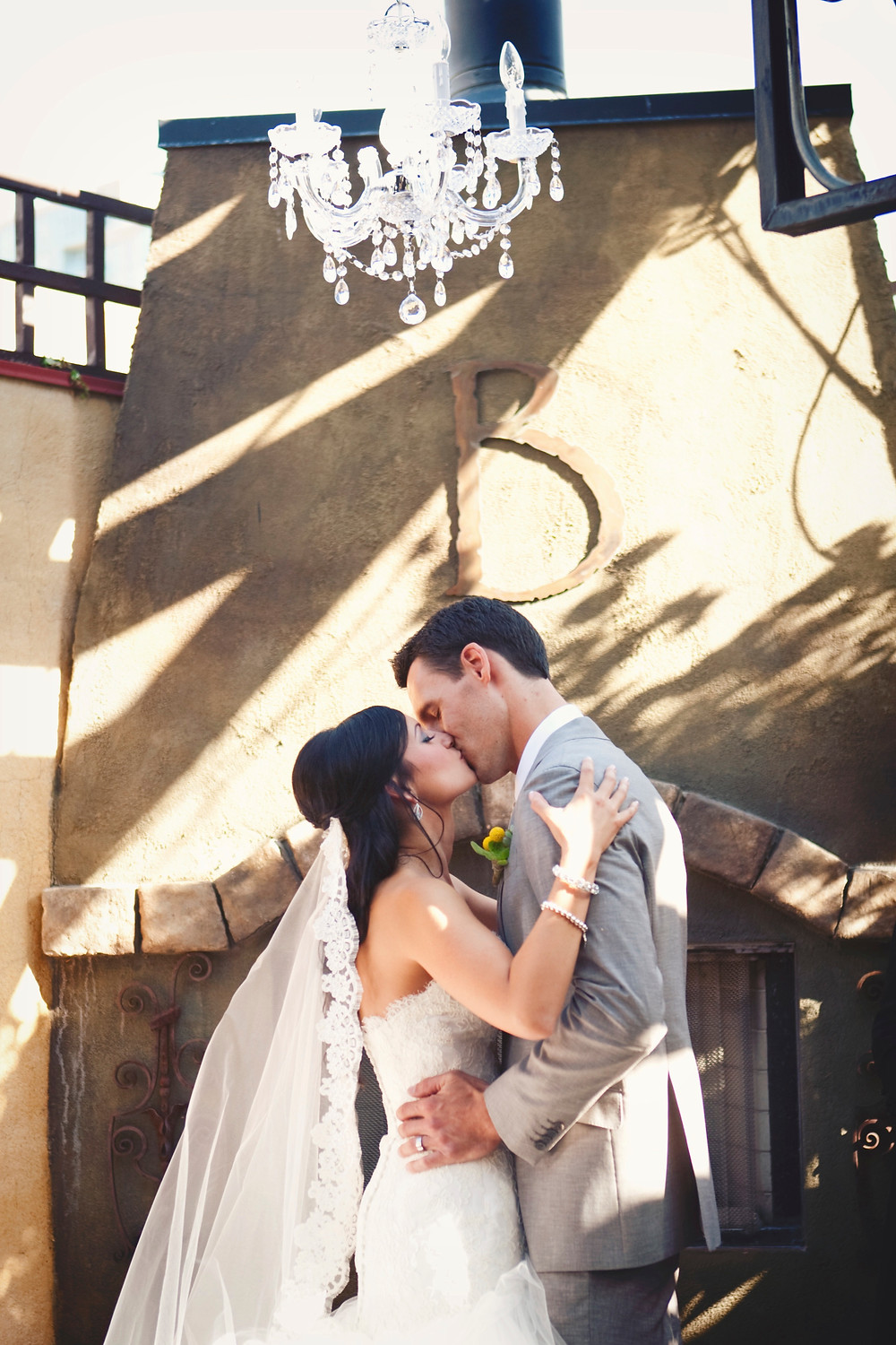 A bride and groom kiss under a crystal chandelier at their rustic Italian inspired wedding.