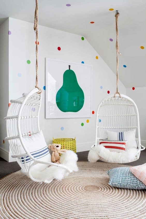 A childrens lounge area with white walls and colourful polka dots with green pear artwork and white boho style hanging chairs and spiral area rug