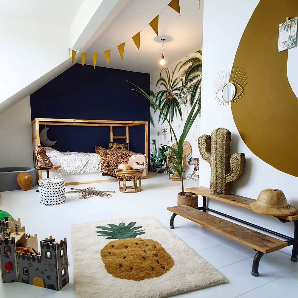 A pineapple rug on white tile floor in a children's jungle themed playroom with cactus and bamboo bedframe with colour blocked walls.