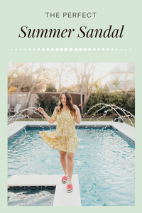 A girl standing outside by a pool in a summer dress.