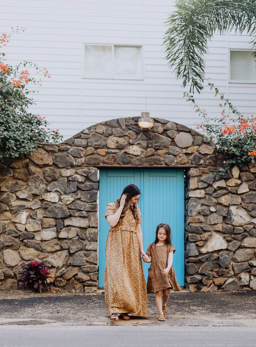 MOTHER AND DAUGHTER WALKING IN FRONT OF A BLUE DOOR