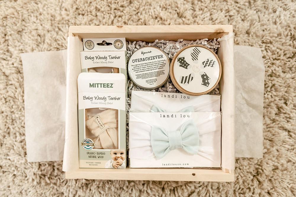 A beautiful custom baby keepsake gift box at a boho baby shower sits on a white rug.