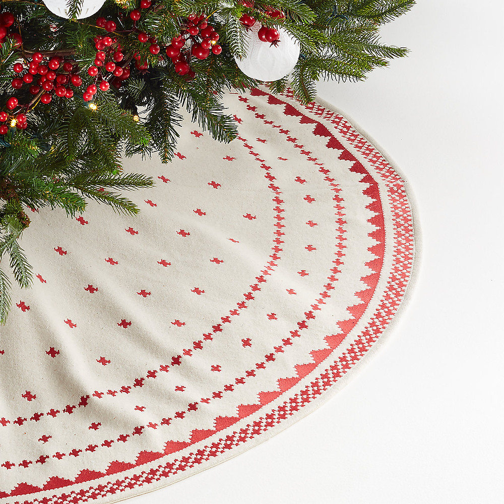 A nordic Scandinavian inspired tree skirt in red and white lays under the Christmas tree decorated with berries in a minimal and modern style.