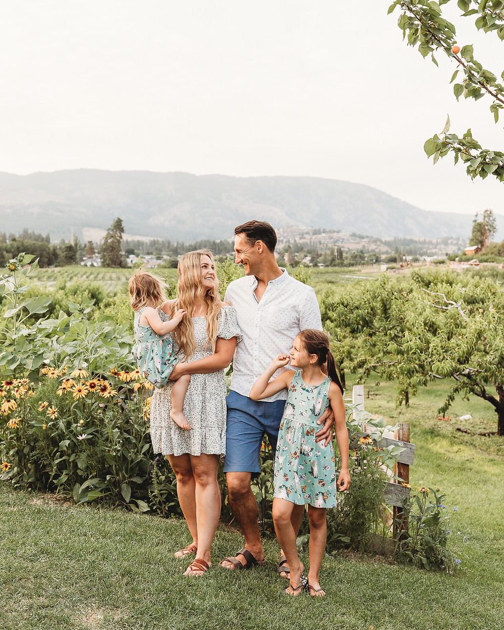 A family stand-in together at a fruit orchard in Kelowna BC at sunset smiling at each other.