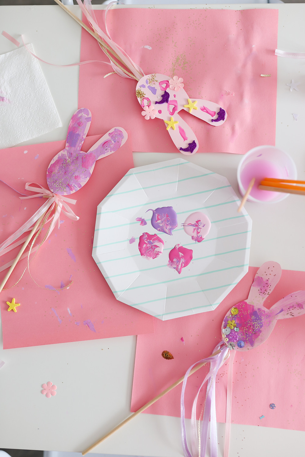A bunny craft at a party table made with pink and purple paint and ribbons.