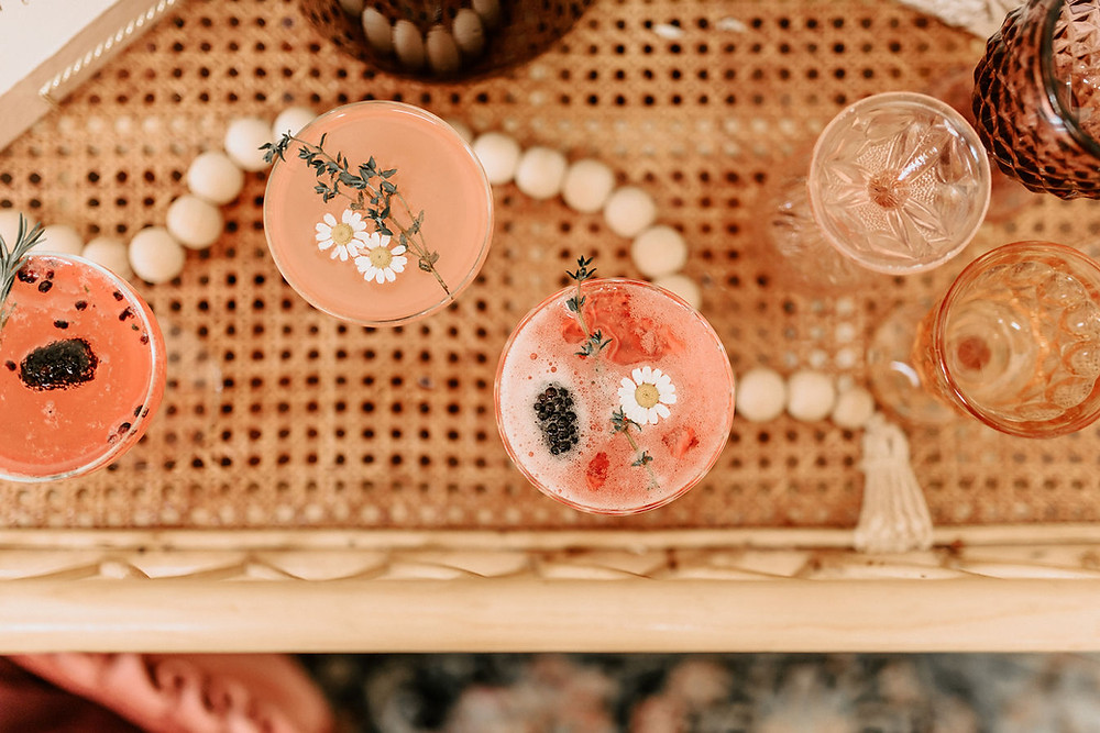 A rattan whicker drink bar cart displays a collection of delicately decorated pink drinks with little flowers sprinkled on top at a boho baby shower.