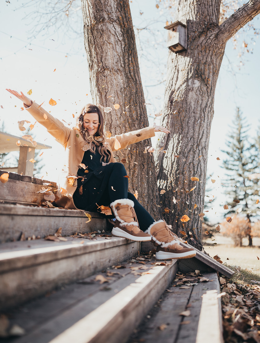 A girl sitting outside on wooden steps tossing leaves up into the air.