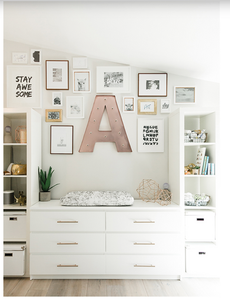 A gallery wall hanging above a white built in shelving unit.