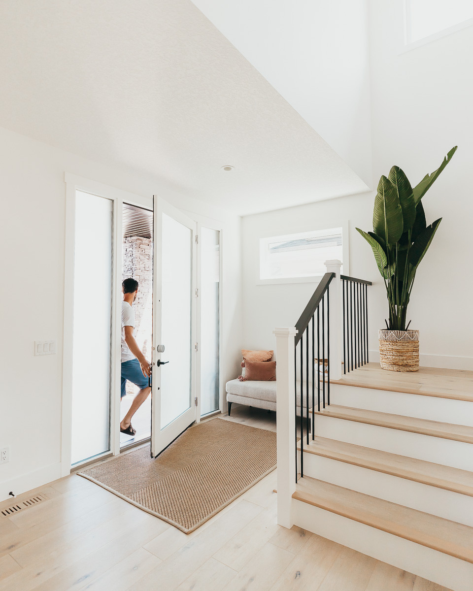 A man leaving out the front door of a modern home with white walls and oak hardwood.
