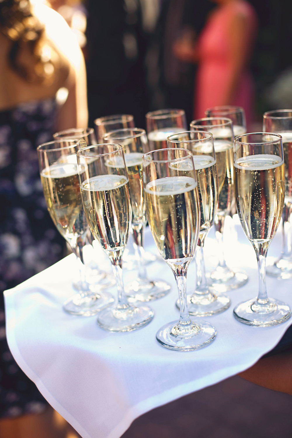 A tray of champagne flutes on a brown tray lined with a white cloth being passed out at a wedding.