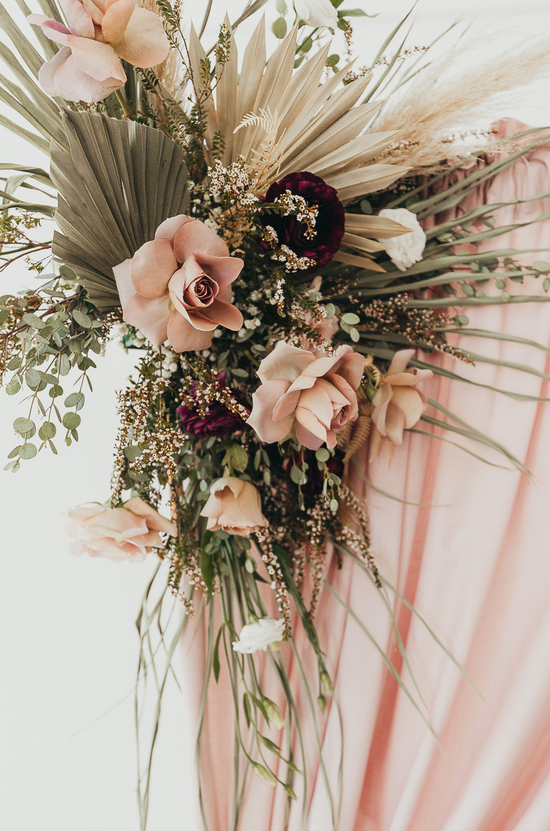 A close up photo of a bouquet of flowers with some dried palm leaves and pampas grasses.