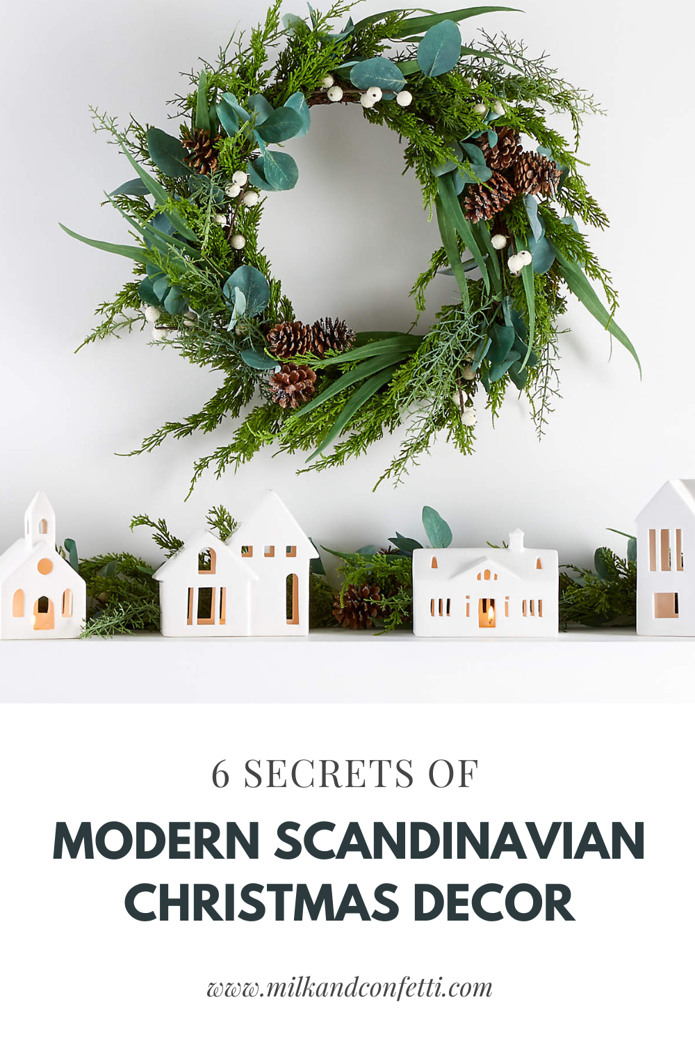 A simple and modern wreath with white berries and pine cones is hung above a fireplace mantel lined with white Scandinavian houses and garland for the Christmas holidays.