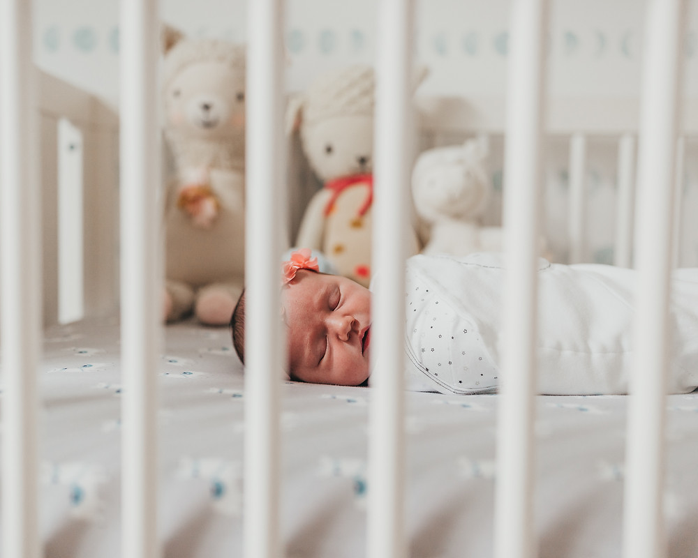 A newborn baby is sleeping in her crib in a swaddle.