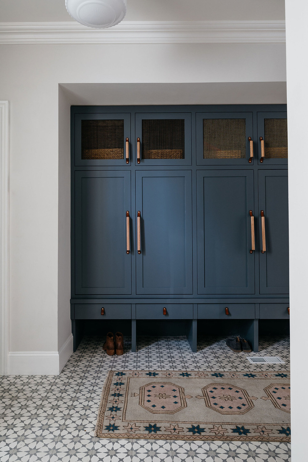 navy blue mudroom cabinets accent concrete tile flooring area rug brass bronze accents