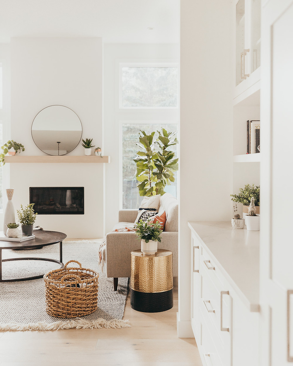 A white Scandinavian living room features natural white oak wood floors with a natural fibre striped wool rug, metal round coffee table, a fiddle leaf fig plant, wicker basket, a gold and black side table with a plant, and a linear fireplace with a natural wood mantel holding a round mirror and some plants.