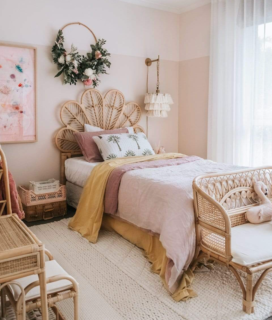 A floral rattan bed frame with some gold, blush and mustard linens in a little girls room with blush walls.