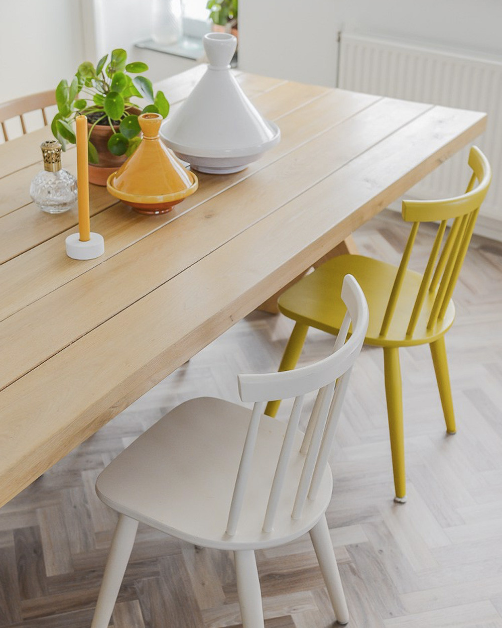 Yellow wooden chair whitewash dining room table white wooden chair vase with plan single candle holder with yellow candle white and yellow tagine on table herringbone flooring