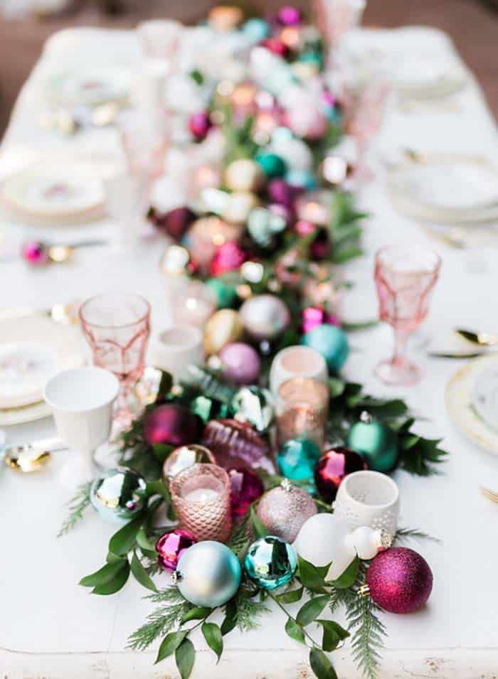 A festive and fun Christmas holiday tablescape decorated with jewel toned ornaments and fresh greenery on a white tablecloth next to pink glasses and gold cutlery.