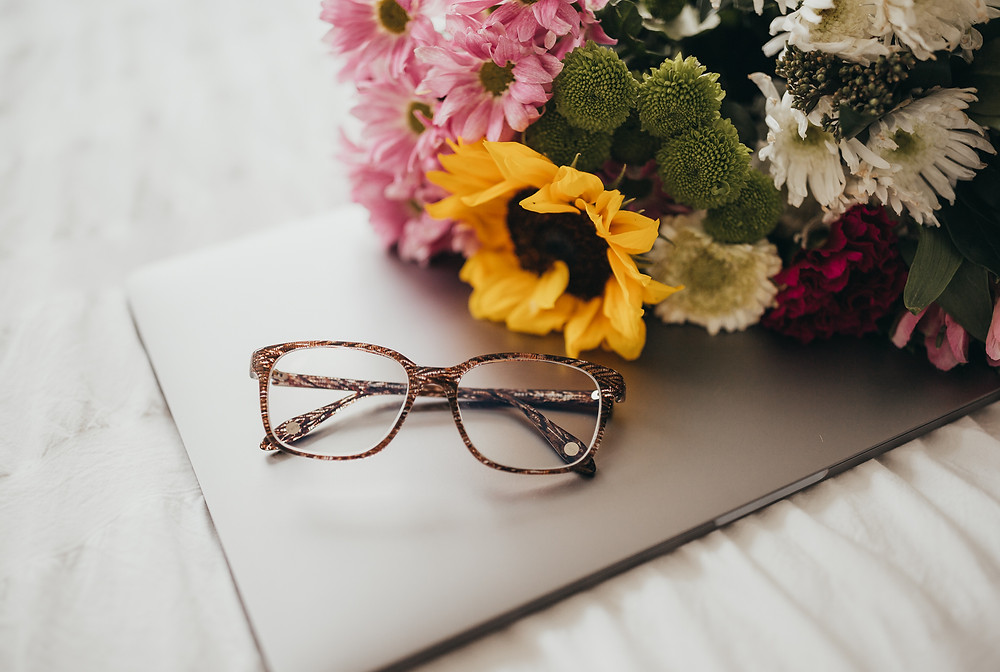 A pair of glasses sitting on a laptop next to some flowers