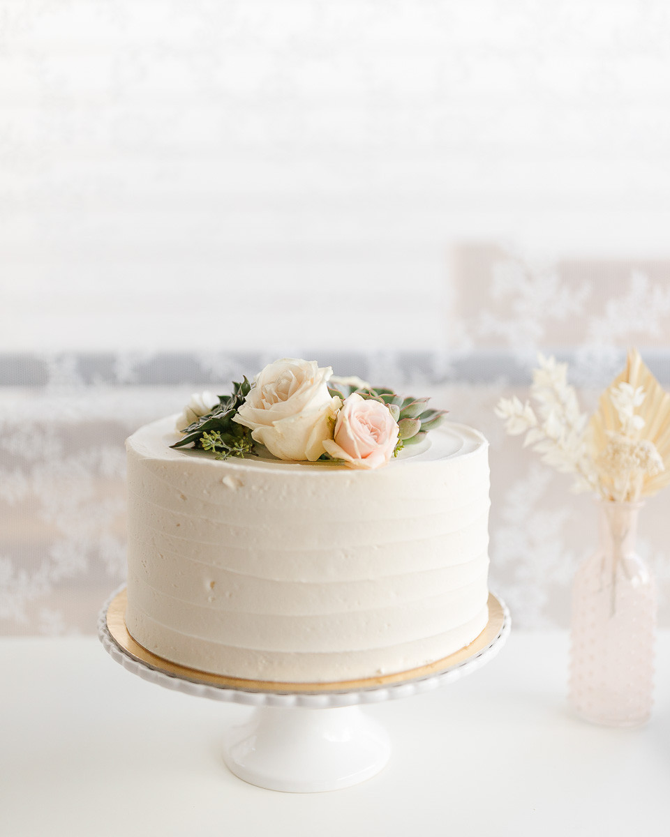 A white cake simply decorated with roses and succulents on a white cake stand in front of a lace curtain.