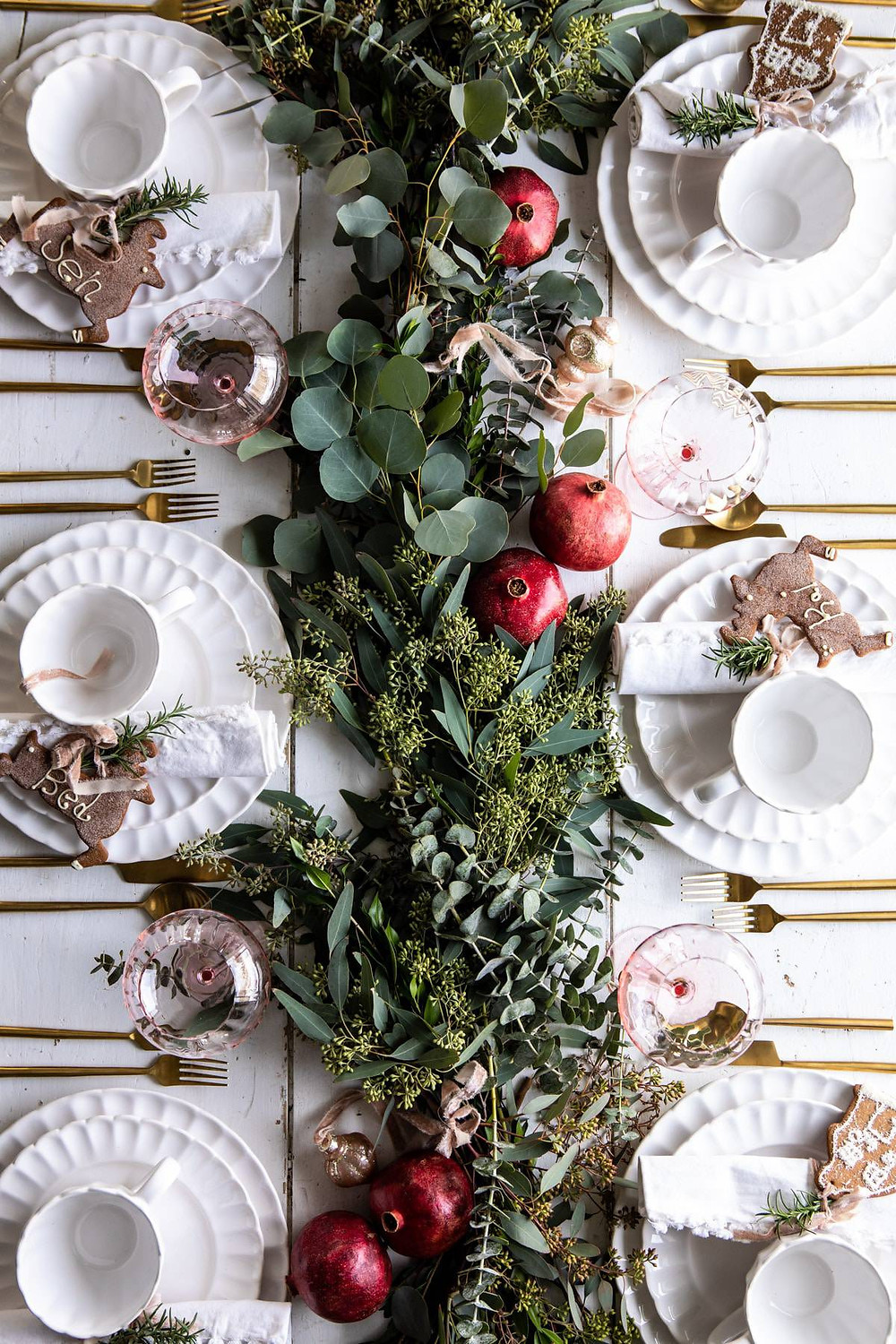 A simple and modern Christmas holiday table decorated with greenery and red pomegranate fruits on a white wood table with white china and gold cutlery.