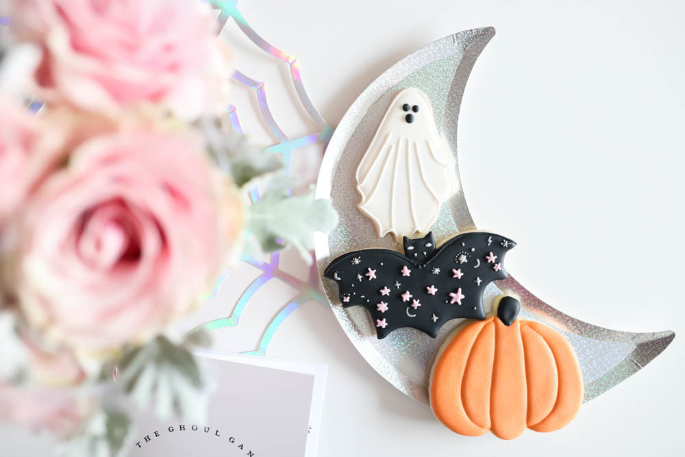 A white kids table at a halloween party decorated with irridescent moon plates and pink roses in a skull vase with some decorated pumpkin, bat and ghost halloween cookies.