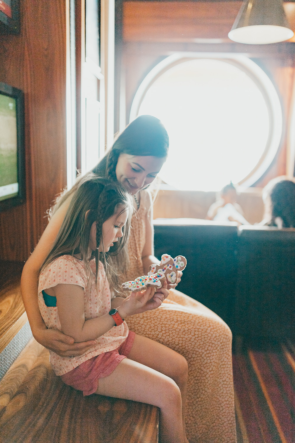 A mother and daughter sitting together looking at a gingerbread cookie they decorated.