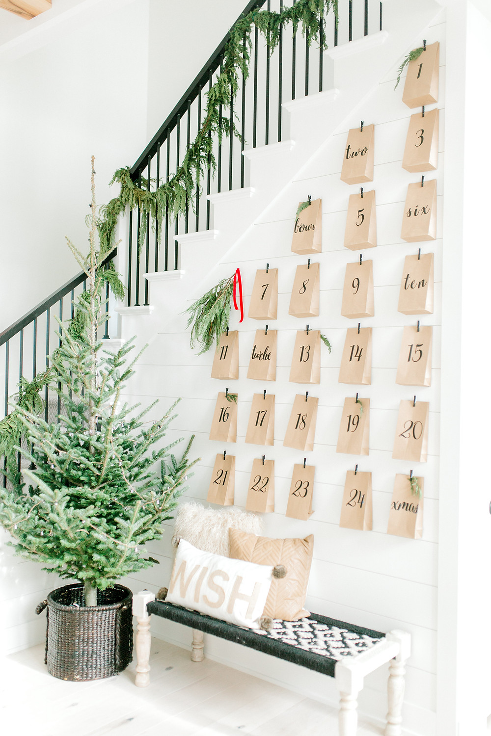 Stairs lined with garland, a small Christmas tree and brown paper bags are hung above a bench.