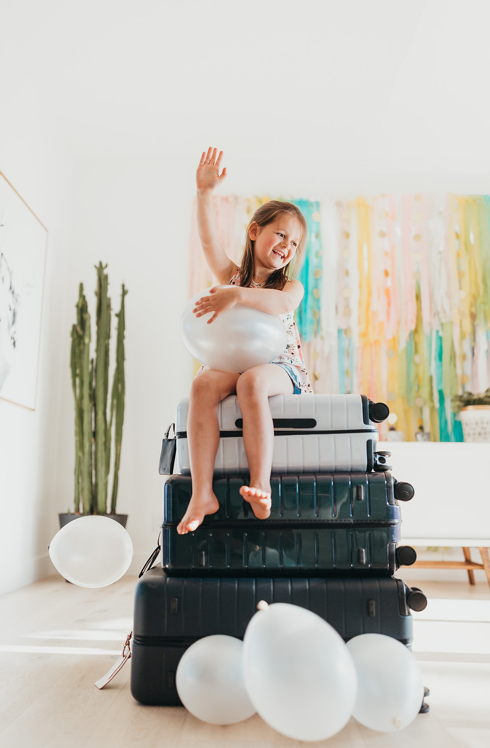 Excited little girl sitting on luggage.