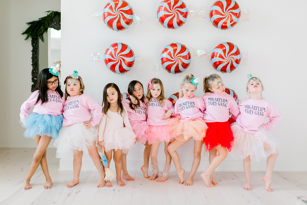 Candy swirl balloons line a wall behind sugarplum fairy gang at a nutcracker party.