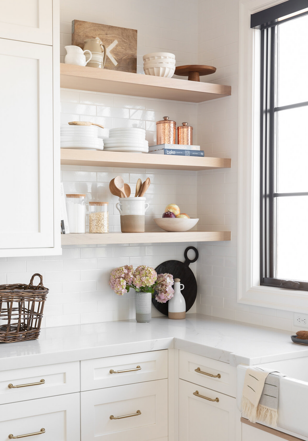 A white kitchen with white oak open shelves beautifully styled with minimal dishes.