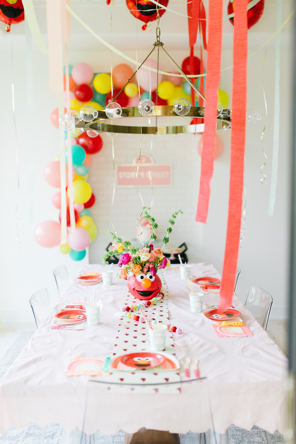 A Sesame Street Elmo birthday party with colourful balloons, streamers over a table with Elmo plates, cups, and napkins with a white table cloth and floral Elmo centrepiece and pink signage.