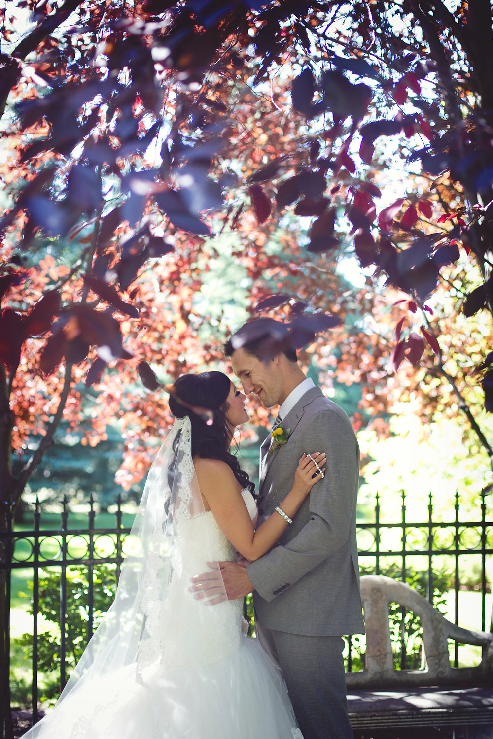 A bride in a tulle and lace wedding dress and a groom in a grey suit standing under some trees next to a fountain on their wedding day.