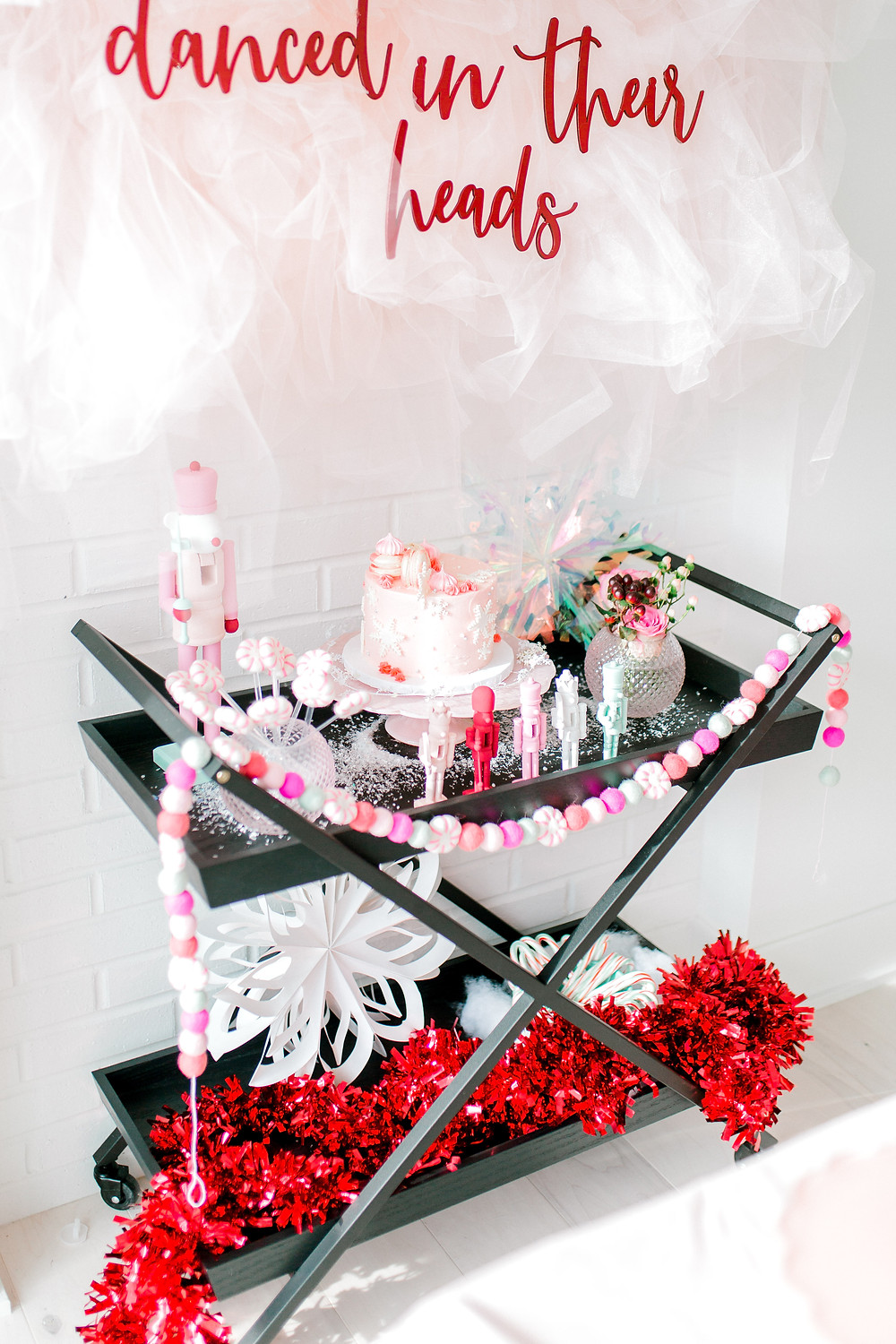 A sugar plums sign with tulle and a bar cart decorated with blue butterfly wings, coloured garland and nutcrackers at a nutcracker birthday.