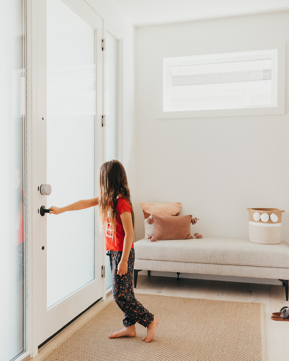 A girl with long hair and a red shirt is standing at her glass front door about to open it to go outside.