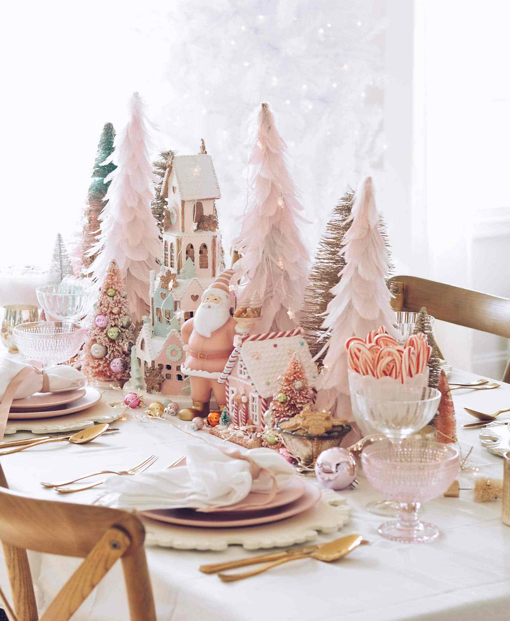 A whimsical Christmas tablescape decorated with blush feather trees, candy canes, Santa ornaments and pastel colors.