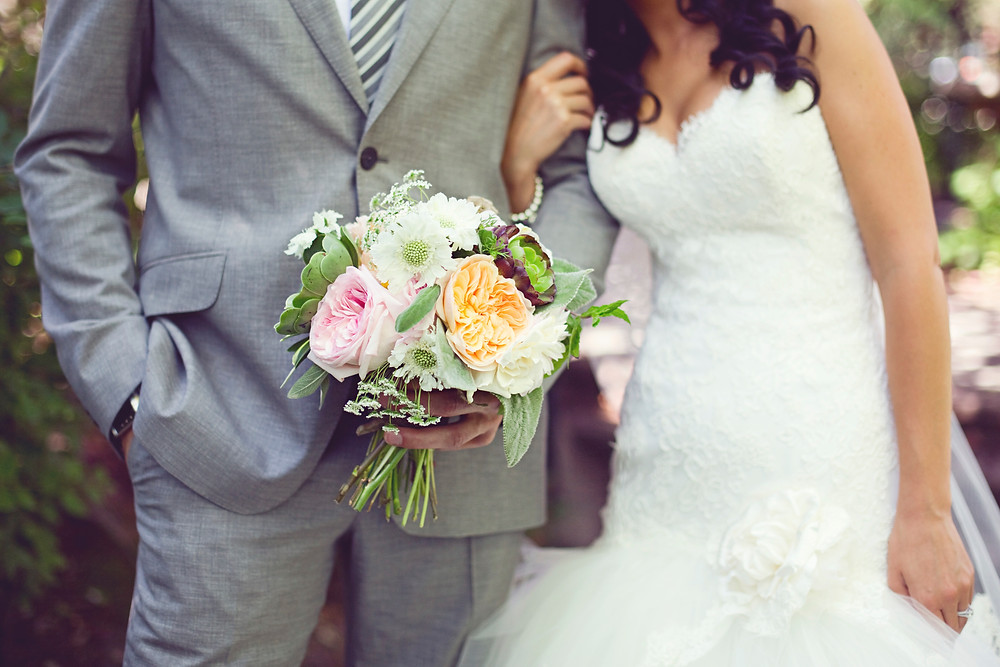 A bride and groom standing together holding a romantic bouquet of flowers.