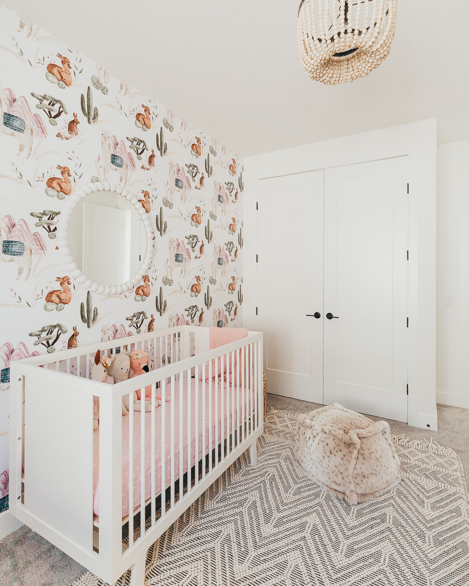 A boho nursery with a white dresser, a wooden ball chandelier, a round mirror and with llama wallpaper.
