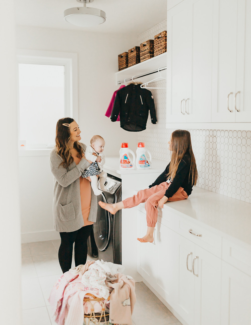 Top must have baby items. A mother and her daughters are doing laundry together in a white laundry room.