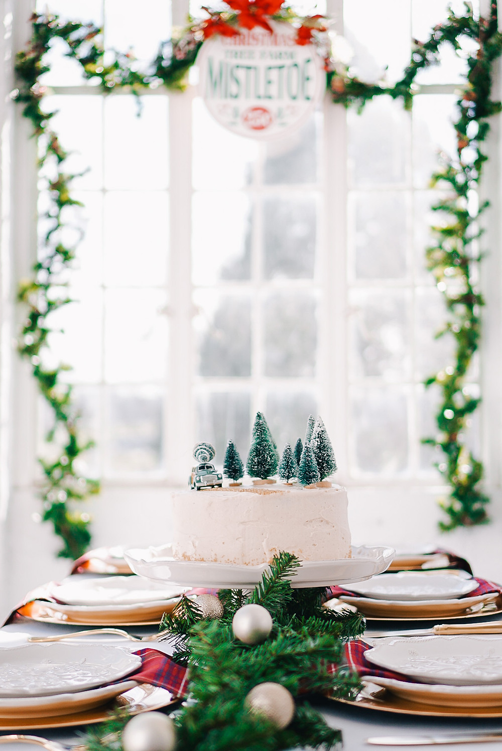 A fun and festive Christmas holiday tablescape with red and green plaid napkins, greenery, ornaments and bottlebrush trees on a white table.
